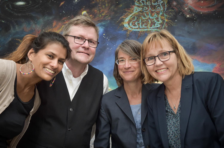 """Foto: ActNow! Das Team von ActNow! von links Rosemary Buch, Ágúst Pétursson, Julia Siebert und Ingibjörg Pétursdóttir vor dem Bild des Künstlers Menem Zantout: """" Die Zusammenkunft"""""""